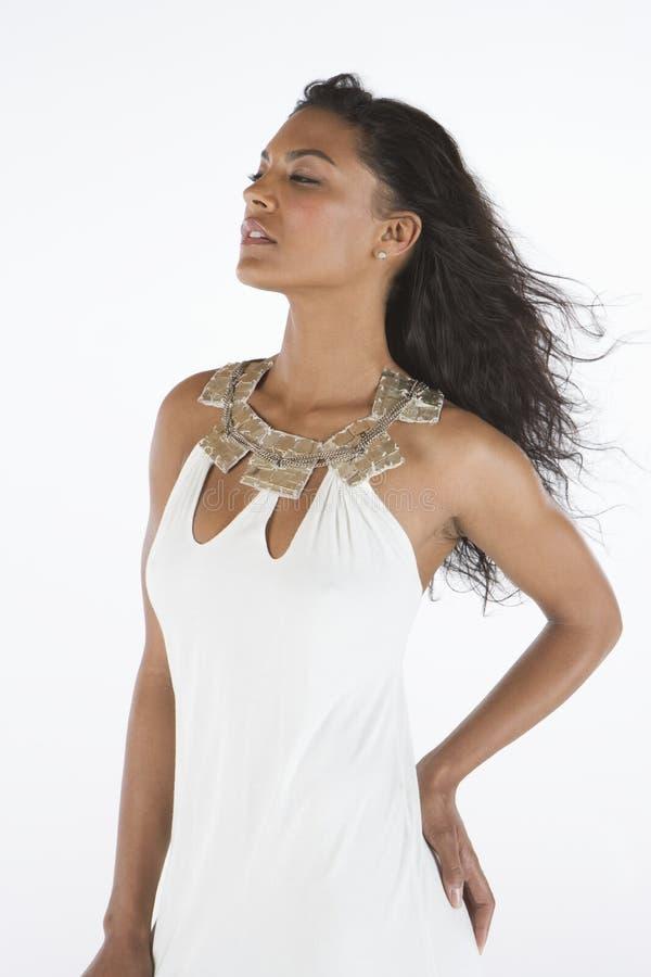 La femme dans la robe blanche se tient avec la main sur la hanche photo libre de droits