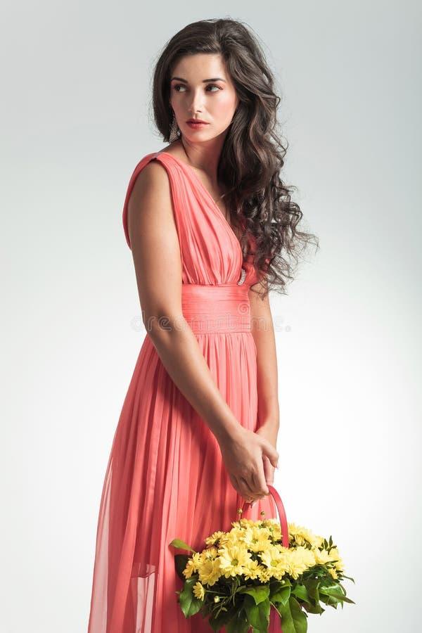 La femme dans la robe rouge tenant le panier de fleur regarde pour dégrossir photographie stock libre de droits