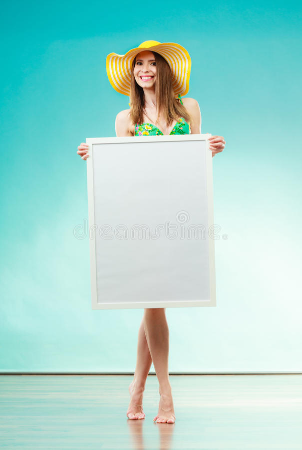La femme dans le bikini tient le conseil de présentation vide photo libre de droits