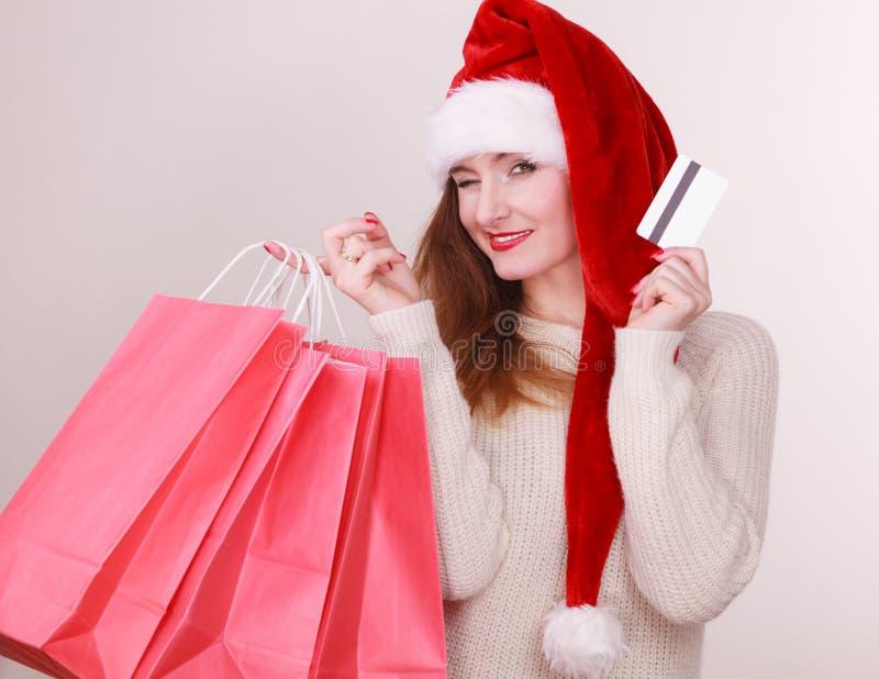 La femme dans le chapeau de Noël tient la carte de crédit et les paniers photographie stock libre de droits