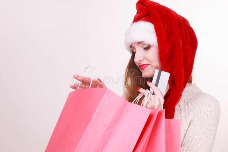 La femme dans le chapeau de Noël tient la carte de crédit et les paniers photographie stock