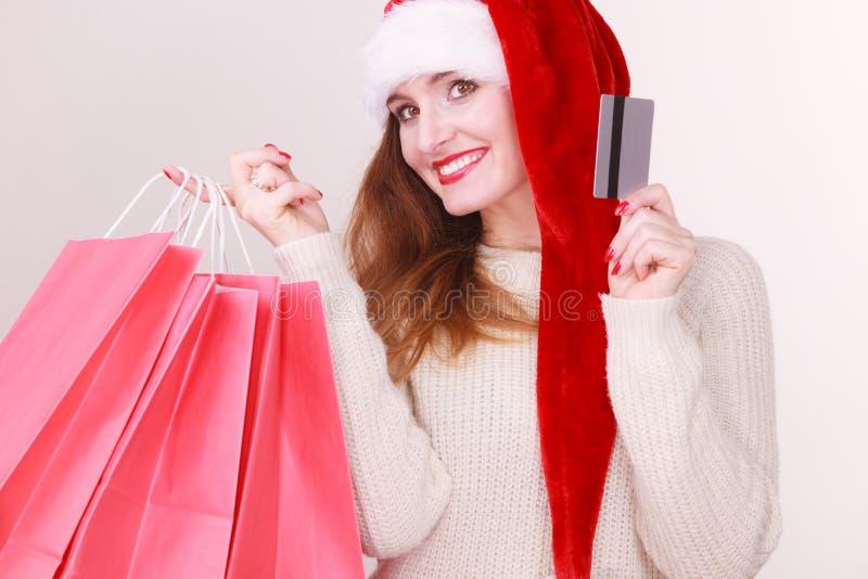 La femme dans le chapeau de Noël tient la carte de crédit et les paniers photos libres de droits