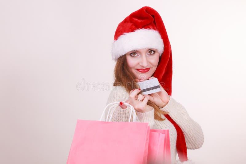 La femme dans le chapeau de Noël tient la carte de crédit et les paniers photos stock