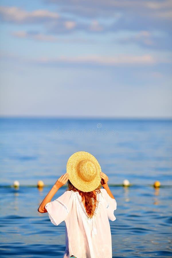 La femme dans le chapeau et le blanc s'habillent en mer photos libres de droits