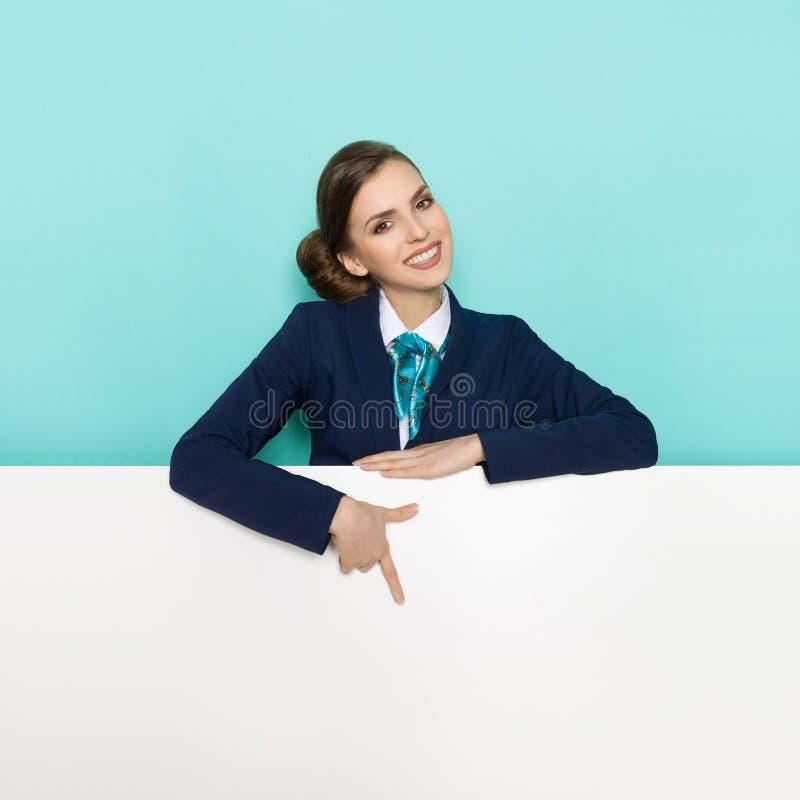 La femme dans le costume bleu se tient derrière la bannière, le sourire et le pointage image stock