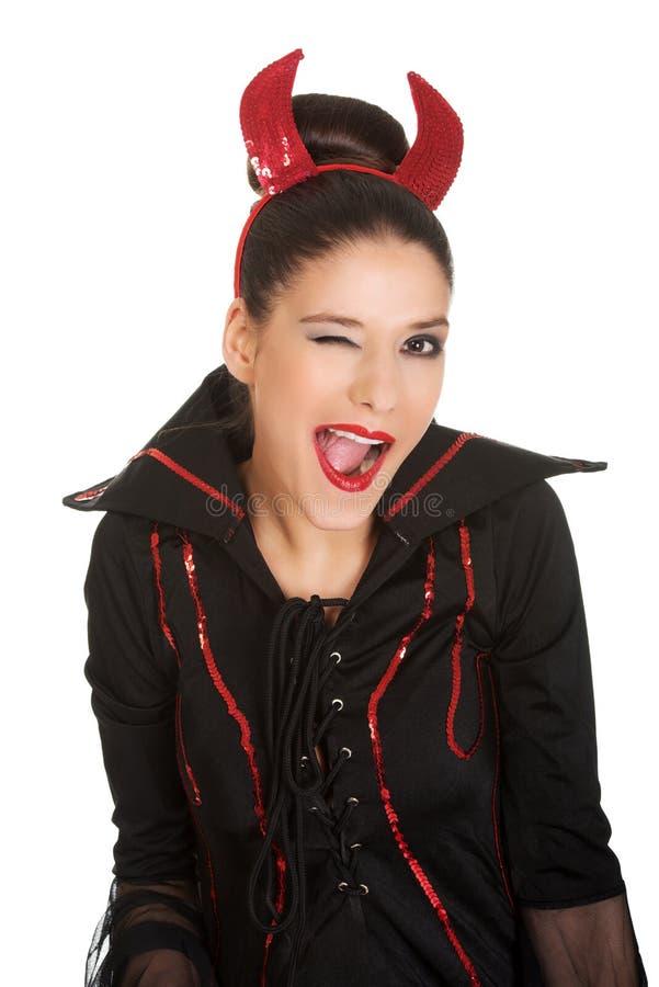 La femme dans le costume de diable clignote l'oeil images libres de droits