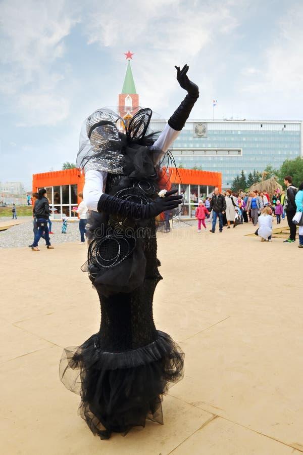 La femme dans le costume noir pose pendant les théâtres de rue montrent la nuit blancs festival d'air ouvert images stock