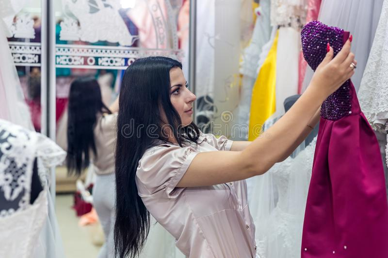 La femme dans le magasin de vêtements choisit égaliser l'équipement image stock