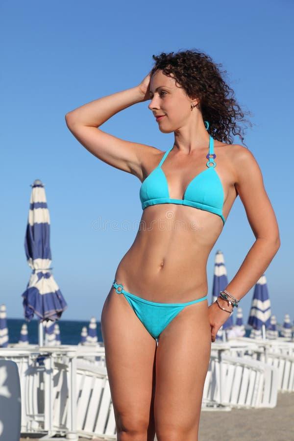 La femme dans le maillot de bain bleu reste sur la plage photo libre de droits
