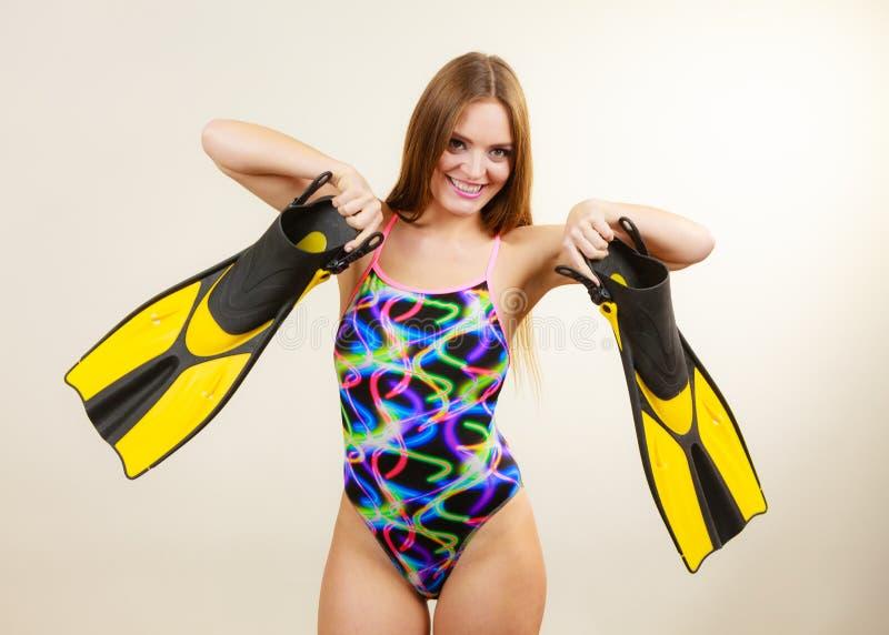 La femme dans le maillot de bain tient des nageoires ayant l'amusement photographie stock