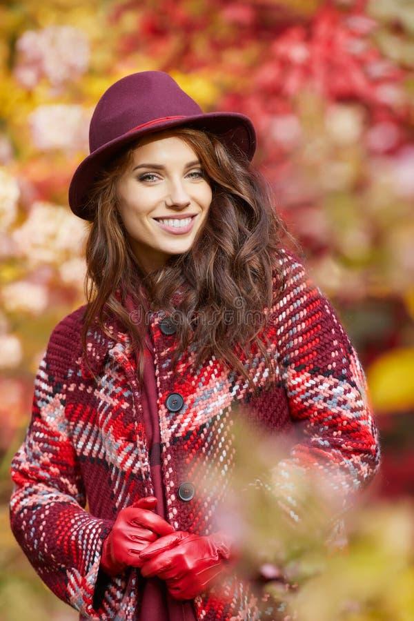 La femme dans le manteau avec le chapeau et l'écharpe en automne se garent images libres de droits