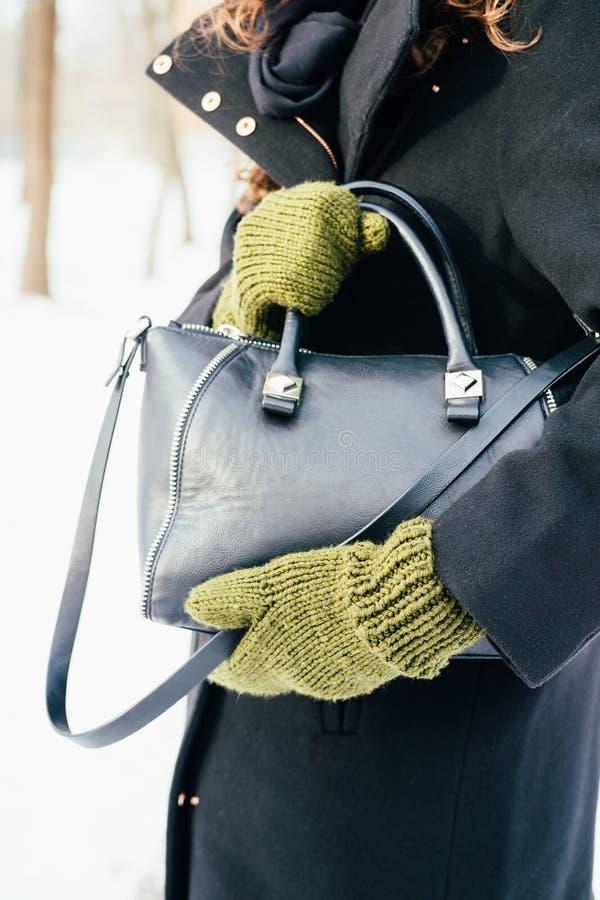 La femme dans le manteau noir et les gants verts juge un sac à main en gros plan image libre de droits