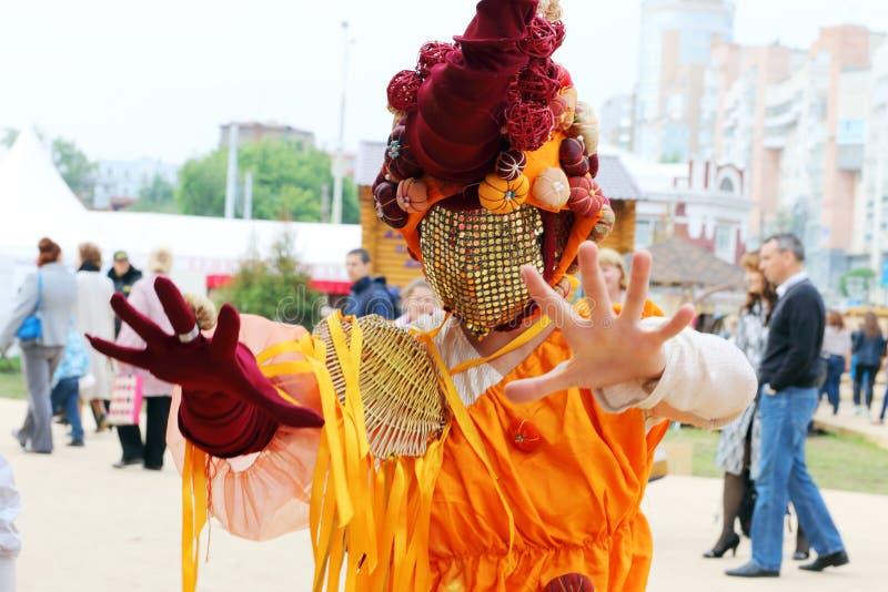 La femme dans le masque peu commun pose pendant les théâtres de rue montrent la nuit blancs festival d'air ouvert image libre de droits