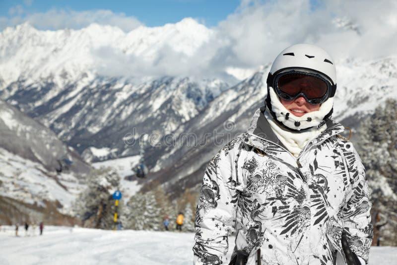 La femme dans le procès et le casque de ski reste contre des montagnes images libres de droits