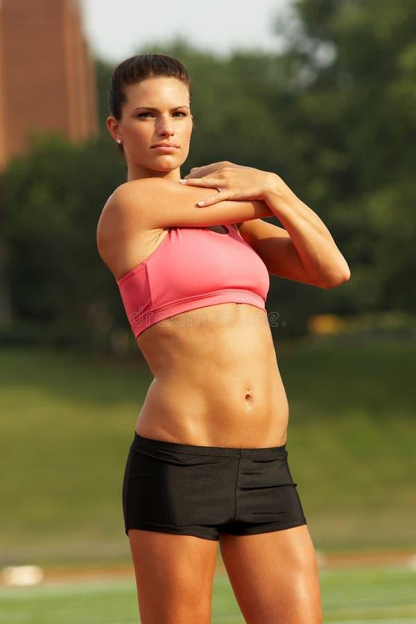 La femme dans le rose folâtre le soutien-gorge étirant le triceps images stock