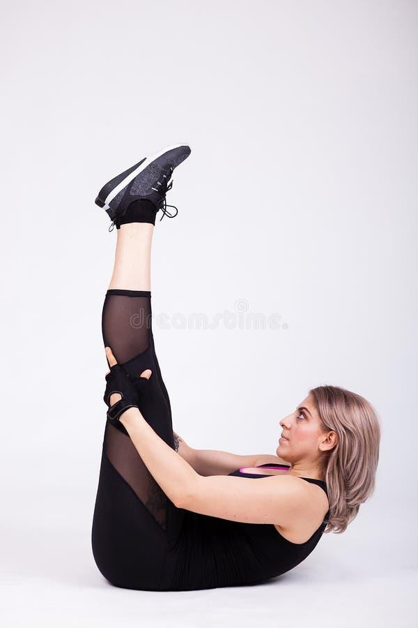 La femme dans le sport vêtx le mensonge sur le plancher se levant ses jambes  photographie stock