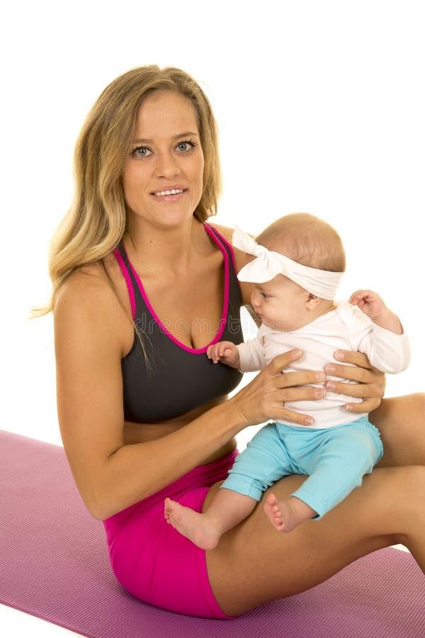 La femme dans le vêtement de forme physique s'asseyent avec le bébé image stock