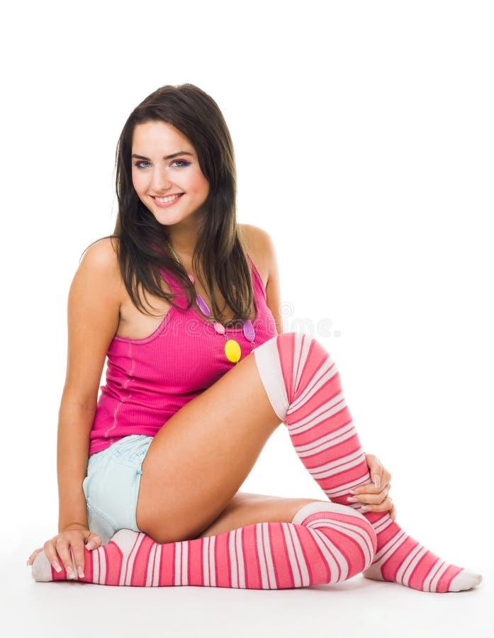 La femme dans les chaussettes roses avec le long cheveu s'asseyent et regardent image stock