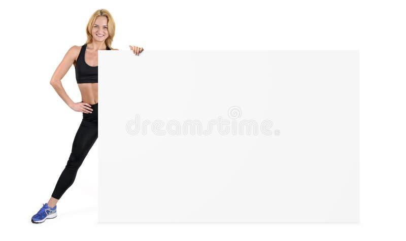 La femme dans les vêtements de sport tient un côté d'une bannière vide énorme d'isolement sur le fond blanc images stock