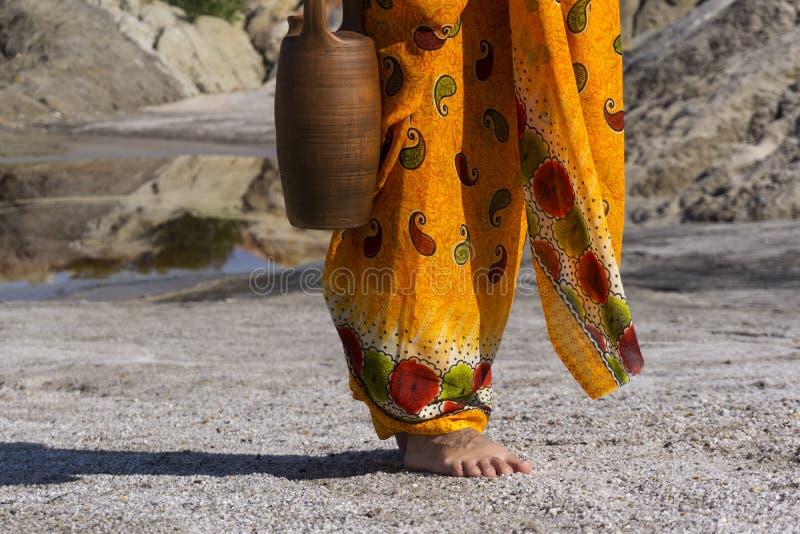 La femme dans la robe ethnique va chercher l'eau photo libre de droits