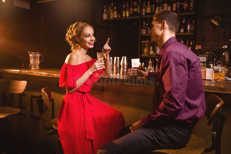 La femme dans la robe flirte avec l'homme dans la boîte de nuit photographie stock