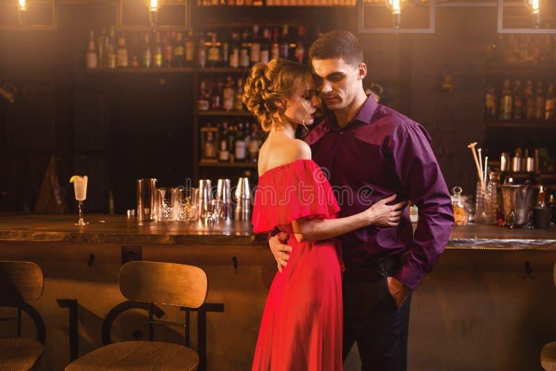 La femme dans la robe rouge étreint avec son homme dans la barre photo libre de droits