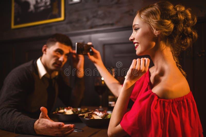 La femme dans la robe rouge fait l'image de son homme au téléphone photo stock