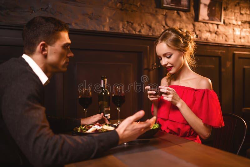 La femme dans la robe rouge fait l'image de son homme au téléphone photo libre de droits