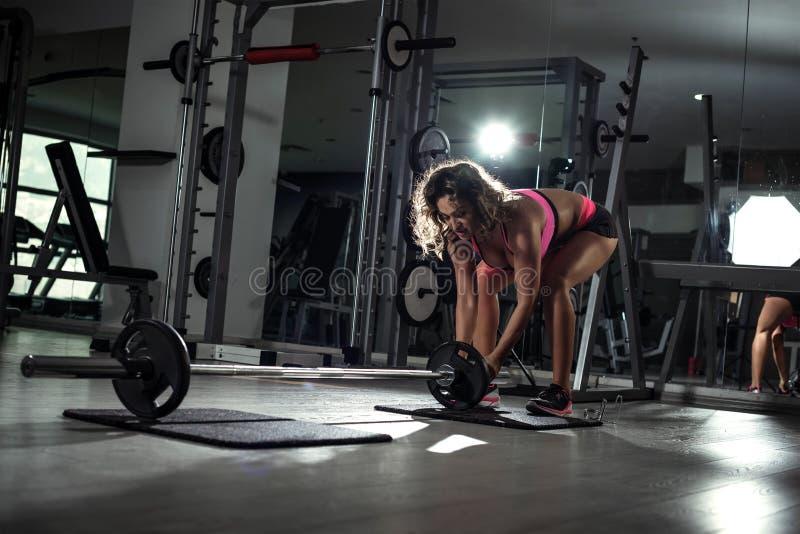 La femme dans 30s en retard plaçant des poids sur le barbell dans le gymnase avant pèsent photos stock