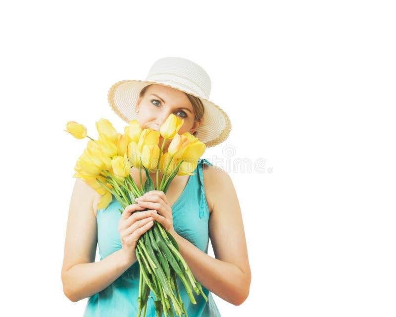 La femme dans un chapeau jette un coup d'oeil par derrière un bouquet des tulipes jaunes de ressort photo stock