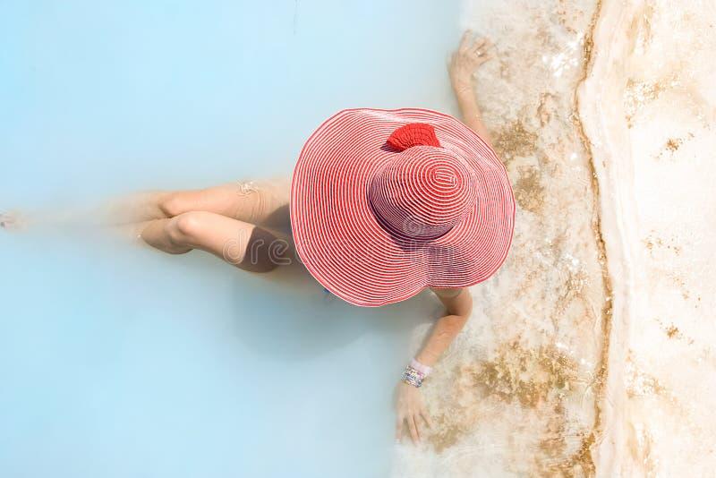 La femme dans un chapeau rouge prend le bain rajeunissant photo stock
