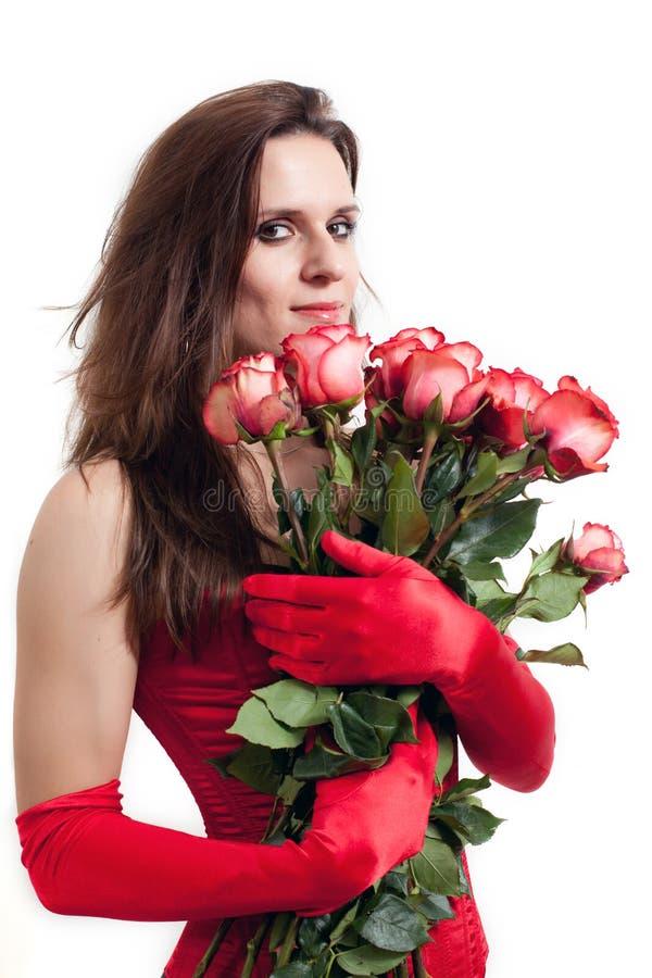La femme dans un corset rouge retient des roses photographie stock libre de droits