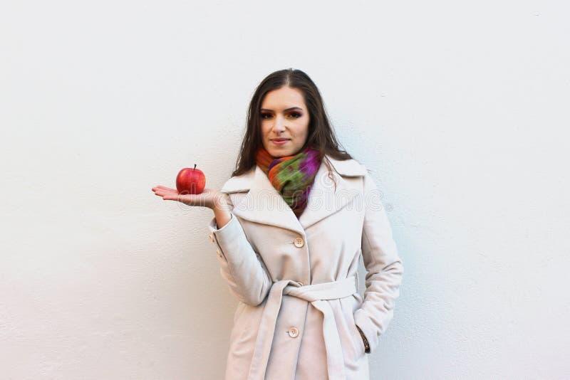 La femme dans un manteau tient une pomme juteuse rouge photos libres de droits
