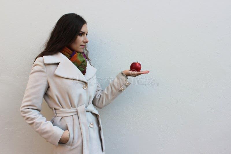 La femme dans un manteau tient une pomme juteuse rouge images libres de droits