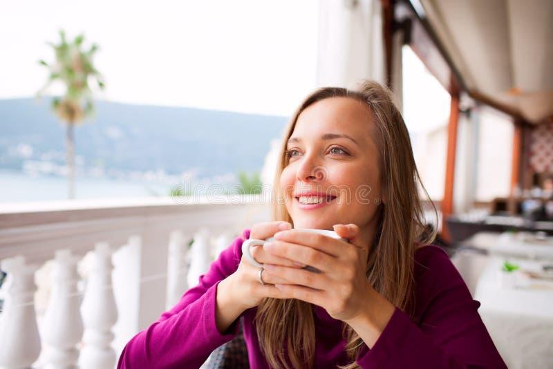 La femme dans un restaurant boit du café photographie stock libre de droits