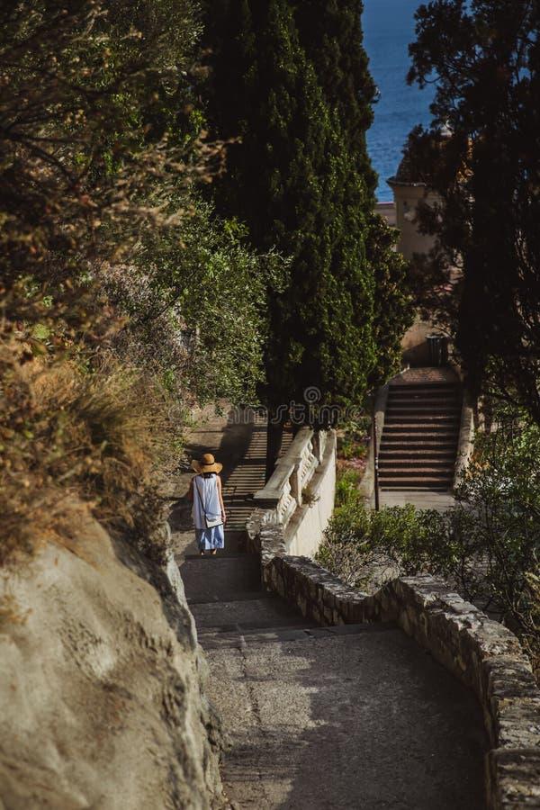 La femme dans une beaux robe et chapeau d'été va en bas des escaliers à la plate-forme d'observation dans la colline ou le parc i image libre de droits