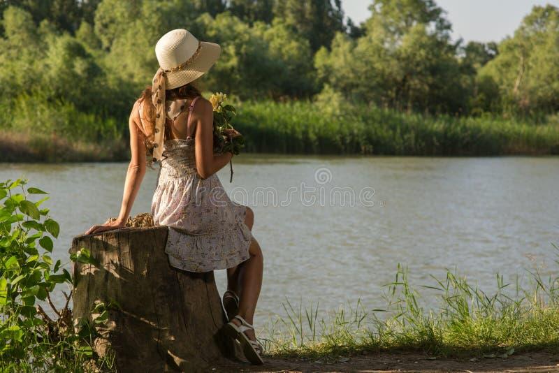 La femme dans une robe et un chapeau s'assied sur la berge sur un tronçon photos libres de droits