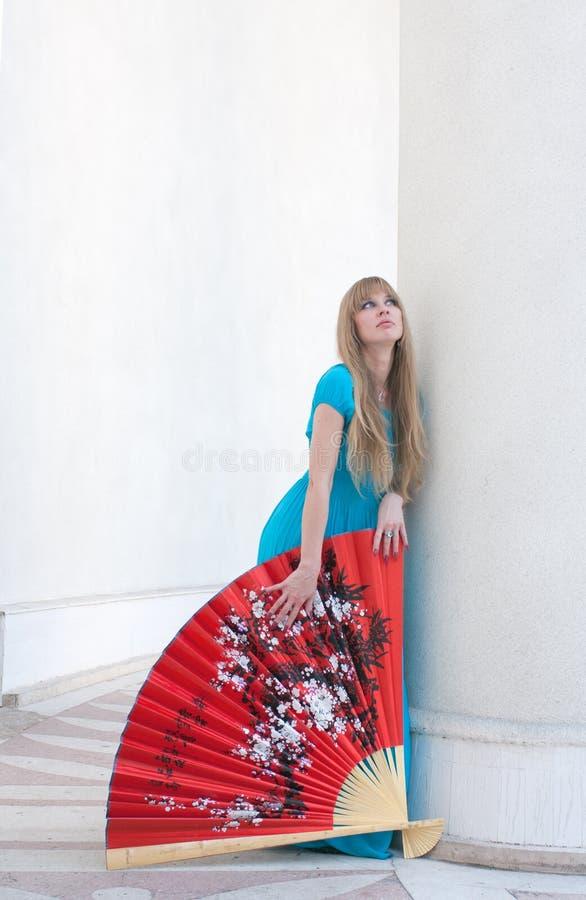 La femme dans une robe et un ventilateur image stock