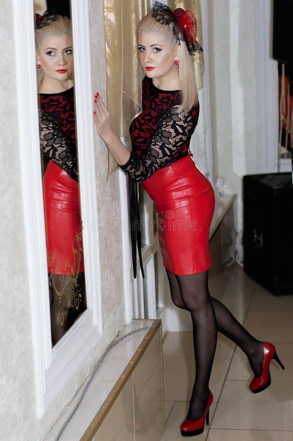 La femme dans une robe rouge, des chaussures rouges et un chapeau rouge image stock