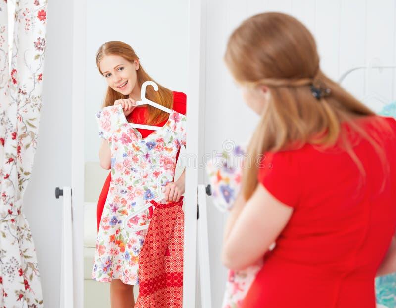 La femme dans une robe rouge regarde dans le miroir et choisit des vêtements photos libres de droits