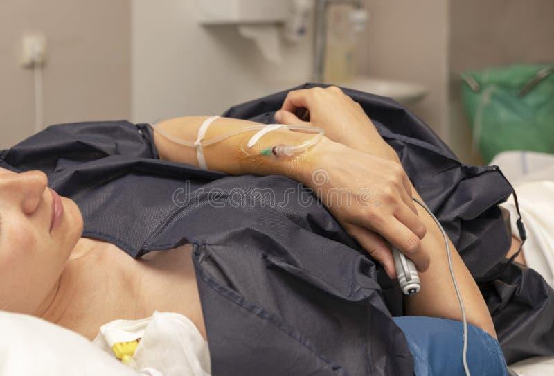 La femme dans une salle d'accouchement avec un compte-gouttes et des presses le bouton à distance pour une dose régulière d'anest photos stock