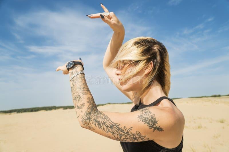 La femme danse dans le désert photo stock