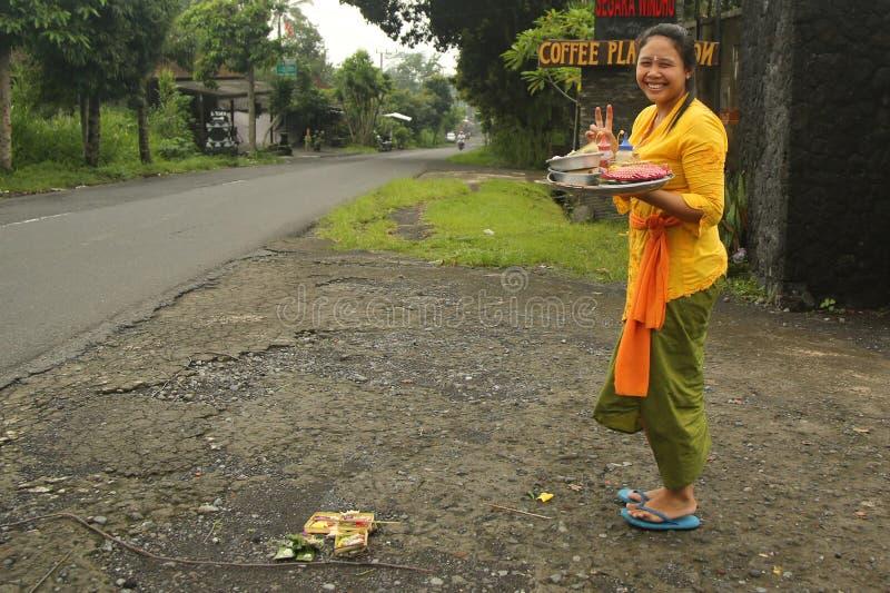 La femme de Balinese apportent des offres des fruits et des cadeaux au temple de village photo stock