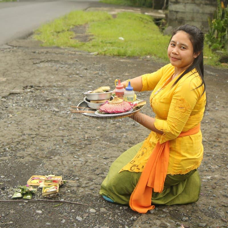 La femme de Balinese apportent des offres des fruits et des cadeaux au temple de village photo libre de droits