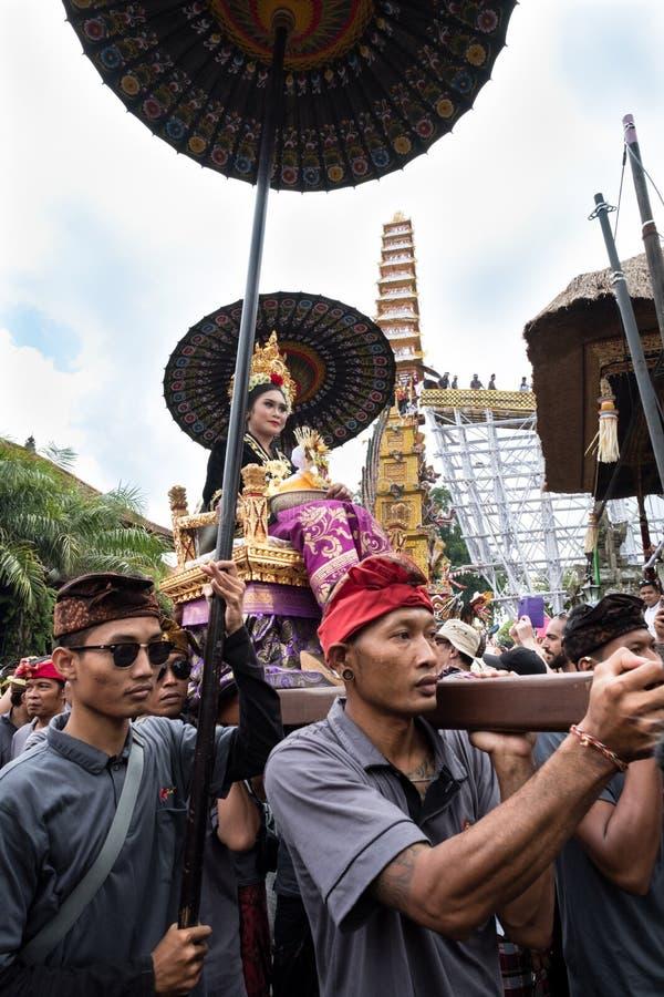 La femme de Balinese s'est habillée dans des vêtements traditionnels a continué un char dans Ubud, Bali pendant l'enterrement de  images stock