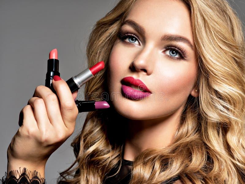 La femme de BBeautiful tient des rouges à lèvres Maquillage Concept de beauté photos stock