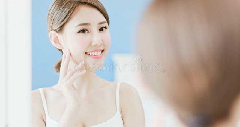 La femme de beauté touchent son visage images stock