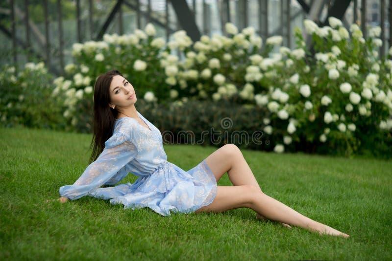 La femme de Bunette s'asseyant sur l'herbe dans le jardin, détendent photo libre de droits