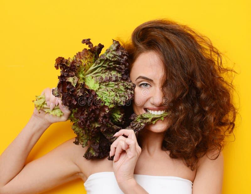 La femme de cheveux assez bouclés mangent de la salade de laitue regardant le coin sur le fond jaune images stock