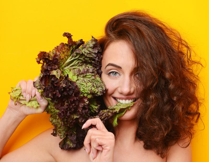 La femme de cheveux assez bouclés mangent de la salade de laitue regardant le coin sur le fond jaune image stock